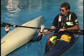 rescuer grabs wrist of paddler and places it on bridging paddle shaft